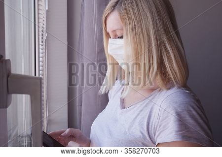 Woman In Surgical Medical Face Mask Staying At Home Near The Window And Using Smartphone, Self Isola