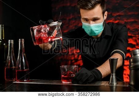 Barman With Mask Masterfully Pours Cold Cocktail Into Glass.