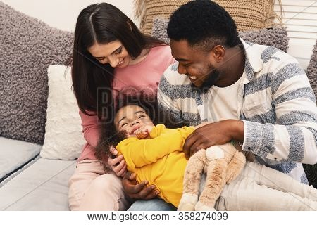 Stay With Family At Home During Quarantine. International Family Having Fun On The Sofa Tickle Daugh