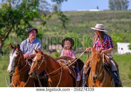 Caminos, Canelones, Uruguay, Oct 7, 2018: Gaucho Family Riding On Horses At A Criolla Festival In Ur