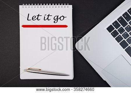 Let It Go Text, Inscription, Phrase Written In A Notebook That Lies On A Dark Table With A Laptop An
