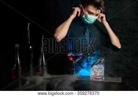 Young Bartender Behind Bar Puts On Medical Mask.