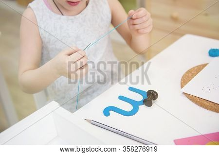 Childrens Hand With A Needle With A Thread And A Blue Letter. Montessori Education. Montessori Schoo