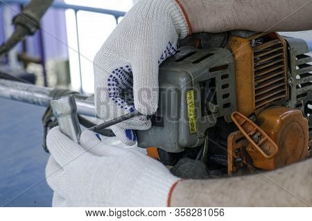 A Master In Working Gloves Repairs The Engine Of An Old Gas Trimmer Using The Screwdriver To Unscrew