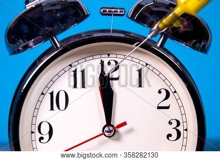 A Large Analogue Clock Counts Down To A Global Event Or Depicts Time Running Out. A Syringe Full Of