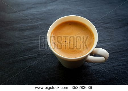 Close Up A Hot Coffee Cup With Foam Crema On A Stone Board Back Color With Copy Space