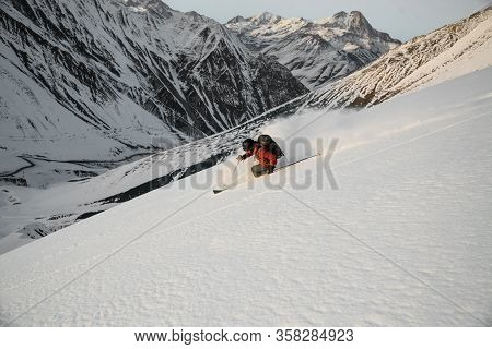 Man Performs Freeride Skiing On Snow-capped Mountains.
