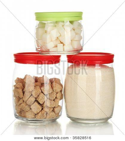 Jars with brown cane sugar lump, white crystal sugar and white lump sugar isolated on white