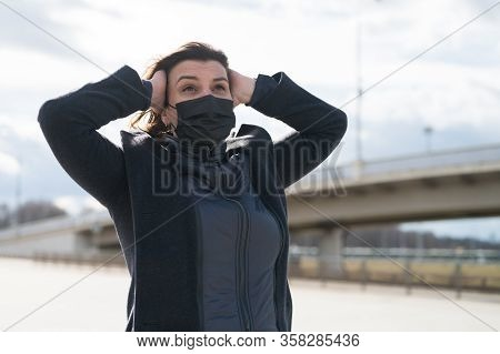 Fashionable Stylish Scared Woman In Protective Black Face Mask, Gray Wool Coat On Street Near Metro