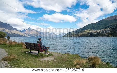 Man Sitting On The Chair Nearly The Waterfront Of Lake Wakatipu In Queenstown, New Zealand. Lake Wak