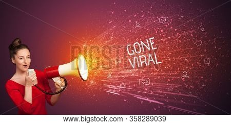 Young woman yelling to loudspeaker with GONE VIRAL inscription, social networking concept
