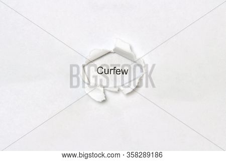 The Word Curfew Printed In Black Letters On A White Sheet Of Paper Is Visible In A Hole Torn In Anot