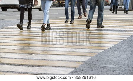 Blurred. People Cross The Road At The Pedestrian Crosswalk At The Intersection. Background