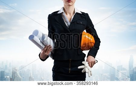 Woman Architect Standing With Construction Drawings And Hardhat. Female Supervisor On Background Of