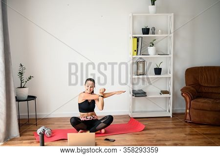 Stay Home. Workout Video Tutorial. A Young Girl Does Exercises And Looks At The Screen Of A Laptop.