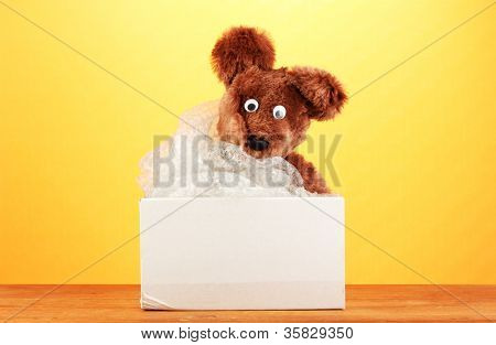 Opened parcel with a child's toy on yellow background close-up