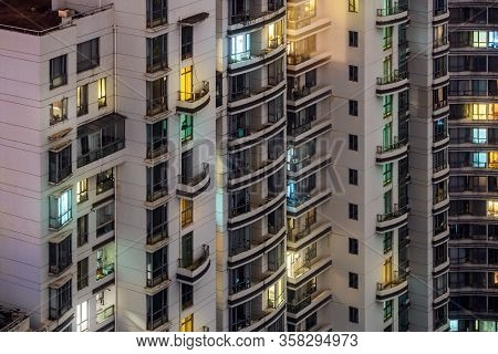 Closeup View Of Highrise At Night Time. Colorful Illuminated Windows. Residential Buildings In Downt