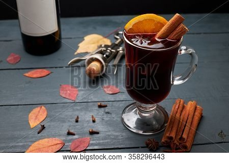 Glass Of Mulled Wine, Bottle Of Wine And Corkscrew With Open Cork On Wooden Table. Hot Red Wine With