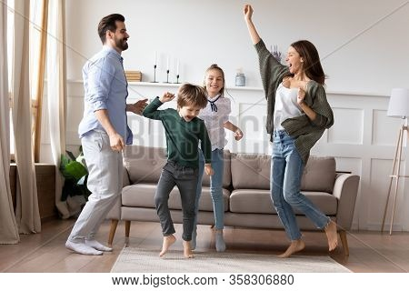 Overjoyed Married Couple Dancing To Favorite Music With Kids.