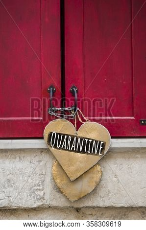 Inscription Quarantine On A Wooden Heart That Hangs On Red Closed Shutters. Quarantine Closure Of Sm