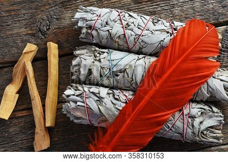 A Close Up Image Of Three White Sage Smudge Sticks And Bright Orange Feather Used In Energy Clearing