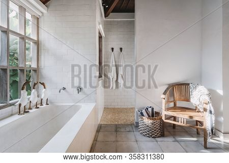 White And Modern Bathroom Interior With Chair, Plaid, Towels On Hook And In Basket, Cute Decor Toys