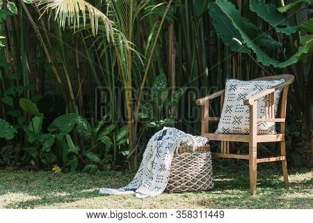 Wooden Traditional Chair With Cushion Standing Near Cozy Decor And Plaid In Wicker Basket On Green B