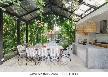 Open Kitchen With Empty Dining Room Table And Chairs Outside, Against Green Fresh Plants On Backgrou