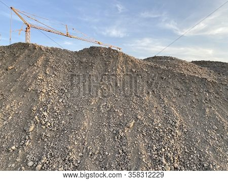 Large Gravel Mound With Construction Crane In The Background