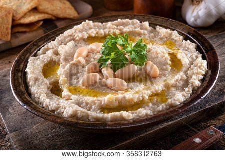 A Bowl Of Delicious Tuscan Style White Bean And Garlic Dip On A Rustic Table Top.