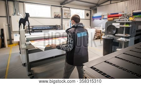 Technician Works In Large Printing Press Hall And Printshop Office