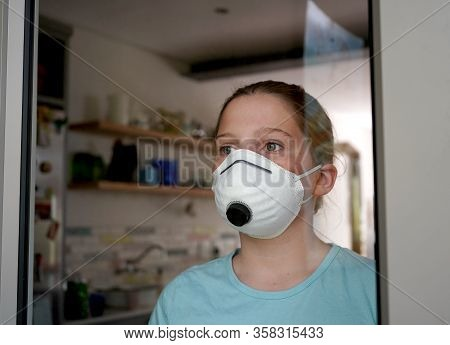 Young Girl At Home In Face Mask, Confined Behind Window