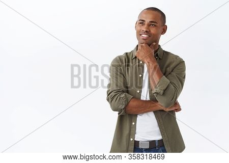 Portrait Of Smart Handsome African-american Man, Touch Chin And Smiling Pleased As Found Excellent C