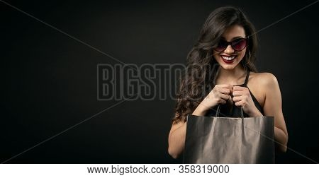 Thrilled Long-haired Lady Holding Shopping Bags With Both Hands In Front Of Chest, Isolated On Black