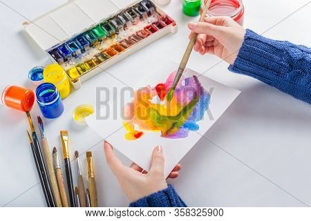Girl Artist Paints With Colored Inks On A White Background Paper. Multicolored Watercolor, Gouache,