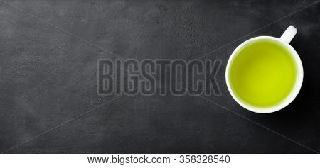 Freshly Brewed Green Tea In Cup .dark Background.top View, Space For Text
