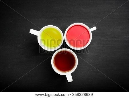 Variety Of Tea In A White Cup On A Dark Background. Red , Green, Black Tea.top View