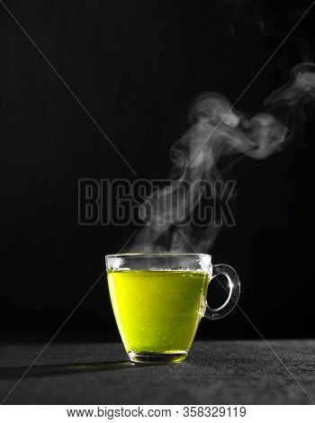 Freshly Brewed Green Tea In A Transparent Glass Cup, Escaping Steam, Darker Background.