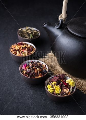 Set Of Different Herbal And Fruit Dry Teas In Clay Bowls, Black Clay Teapot, Dark Moody, Stone, Conc