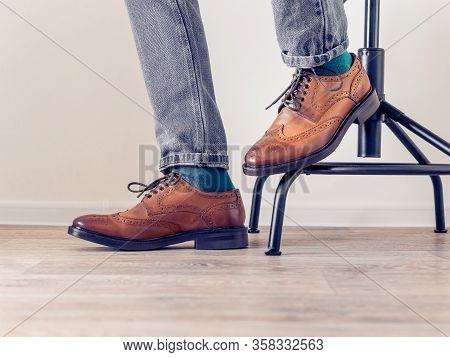 A Man In Brown Brogs And Blue Socks Sits On A Chair