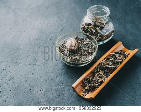Dry Green Tea Leaves On A Wooden Spoon And In A Glass Jar On A Dark Background.