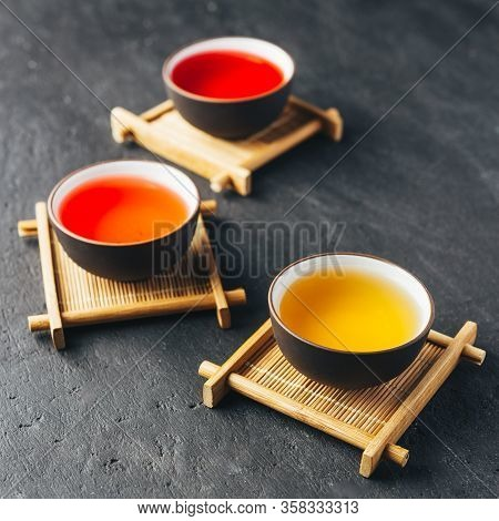 Set Of Different Herbal And Fruit Teas In Clay Bowls On Bamboo Stands. Dark Moody.dark Stone Concret