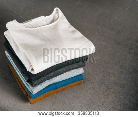 Pile Colorfull Of Sweaters On The Gray Couch. Mens Textile Clothing.