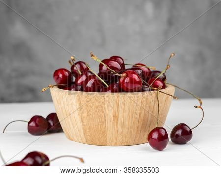 Cherry On A Wooden Plate On A White Background