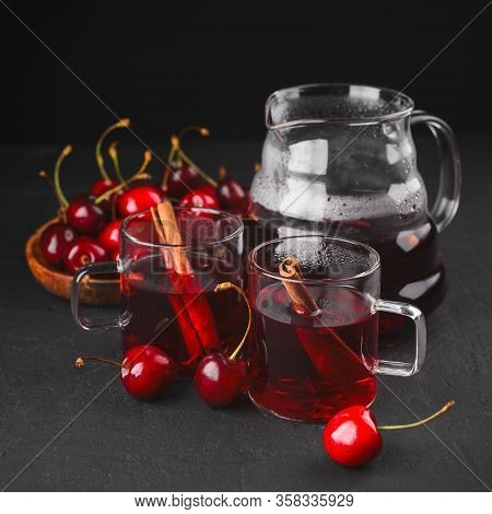 Freshly Brewed Tea With Cherries On A Dark Concrete Background