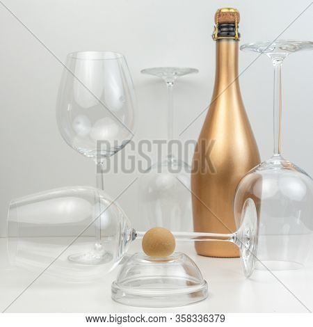 Creative Composition With Marzipan Dessert, Glass Goblets And A Golden Bottle Of Champagne.