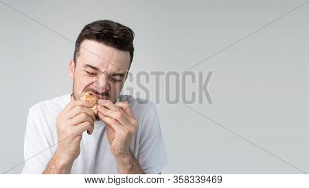 Young Man Isolated Over Background.biting And Chewing Tasty Delicious Burger Alone In Studio. Pleasu