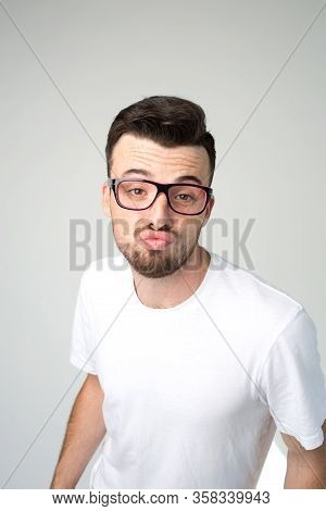 Young Man Isolated Over Background. Strange Weird Guy Look Stright Through Glasses And Hold Lips In