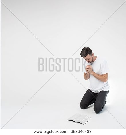 Young Man Isolated Over Background. Guy Stand On Knees And Pray In Front Bible. Studying Word Of God