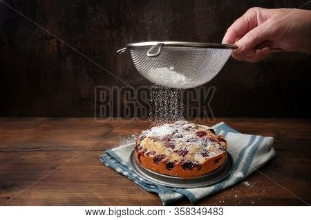 Hand Of A Woman Sieves Icing Sugar On A Freshly Baked Small Cherry Cake, Rustic Wood And Dark Backgr